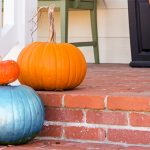 A close-up of a brick front porch with a white railing on one side. Next to the railing are three pumpkins - two orange and one blue.