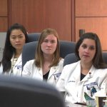 Four students from Penn State College of Medicine's University Park Regional Campus are seen seated at a conference table.