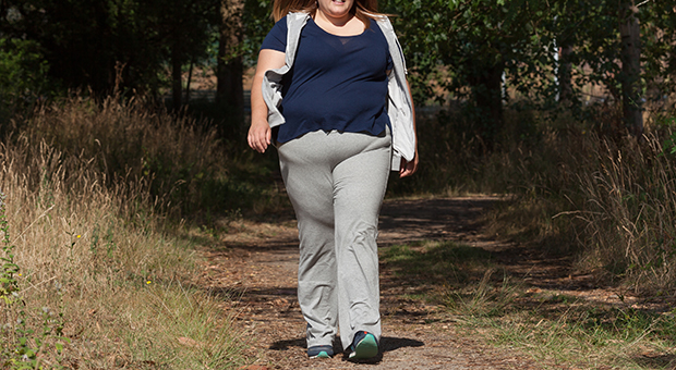 An overweight woman is pictured walking outdoors.