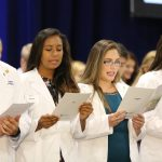 Four students in white coats are seen reciting a pledge at the 2016 White Coat Ceremony.