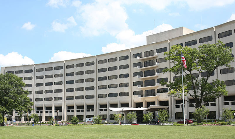 The Penn State College of Medicine Crescent facade is seen at 500 University Drive in Hershey, PA, framed by grass below and a blue sky with clouds above. In front of the building to the right, two flagpoles can be seen displaying the American and Pennsylvania flags.