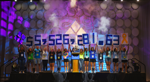 Students stand on stage holding up placards spelling out $5,526,281.63, indicating the amount of money raised through the Four Diamonds Mini-THON in 2016.