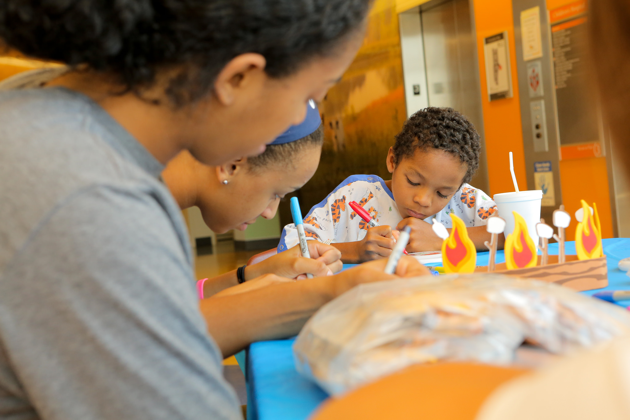 A member of the Penn State women's basketball team sits a table coloring with with two children who are wearing hospital gowns.