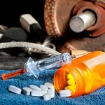 A syringe sitting atop a spilled bottle of pills on top of a blue rag, with a rusted weightlifting plate attached to a bar sitting next to jump ropes in the background.