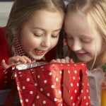Two girls look excitedly into a reusable lunch bag (red, with white polka dots) as the one clutches orange juice.