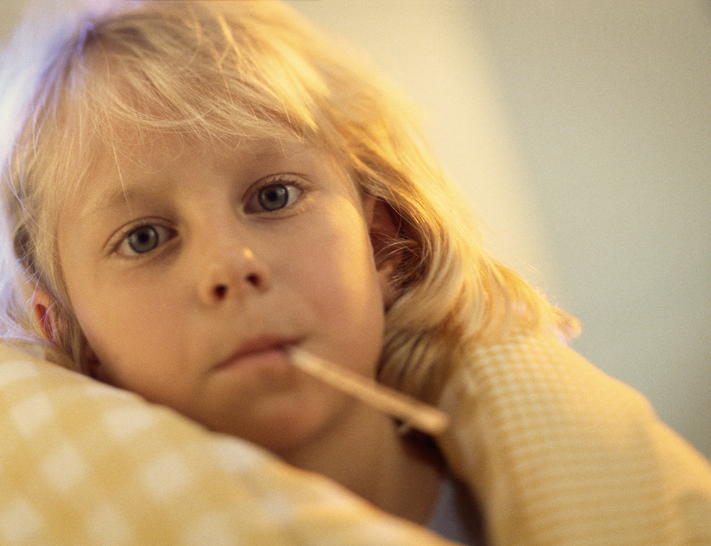A young girl with a thermometer in her mouth is wrapped in a blanket, and looks at the camera.