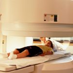 A young boy lays on a platform awaiting an imaging test; a medical professional is closeby.