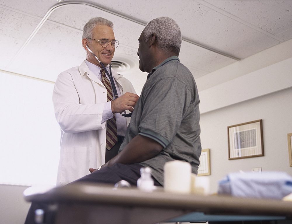 Male doctor examining a male patient.