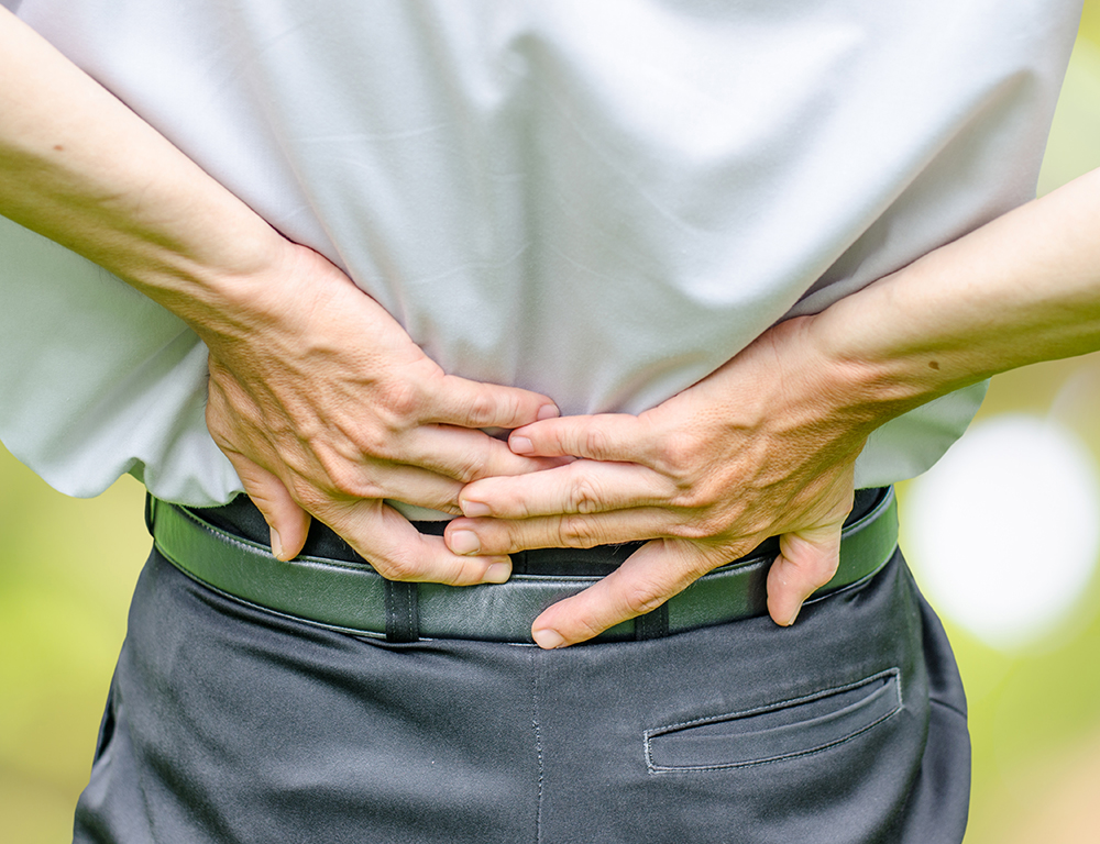 Close up of a man holding his back in pain, isolated on white background.