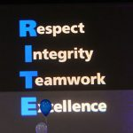 At each year's Inspired Together assembly, faculty, students and staff are honored for exemplifying the organization's RITE values of respect, integrity, teamwork and excellence. The 2016 awards assembly is pictured, with the RITE values projected onto a blue screen between the images of two Nittany Lion shields. People attending the assembly are seen in a crowd in front of the screen.