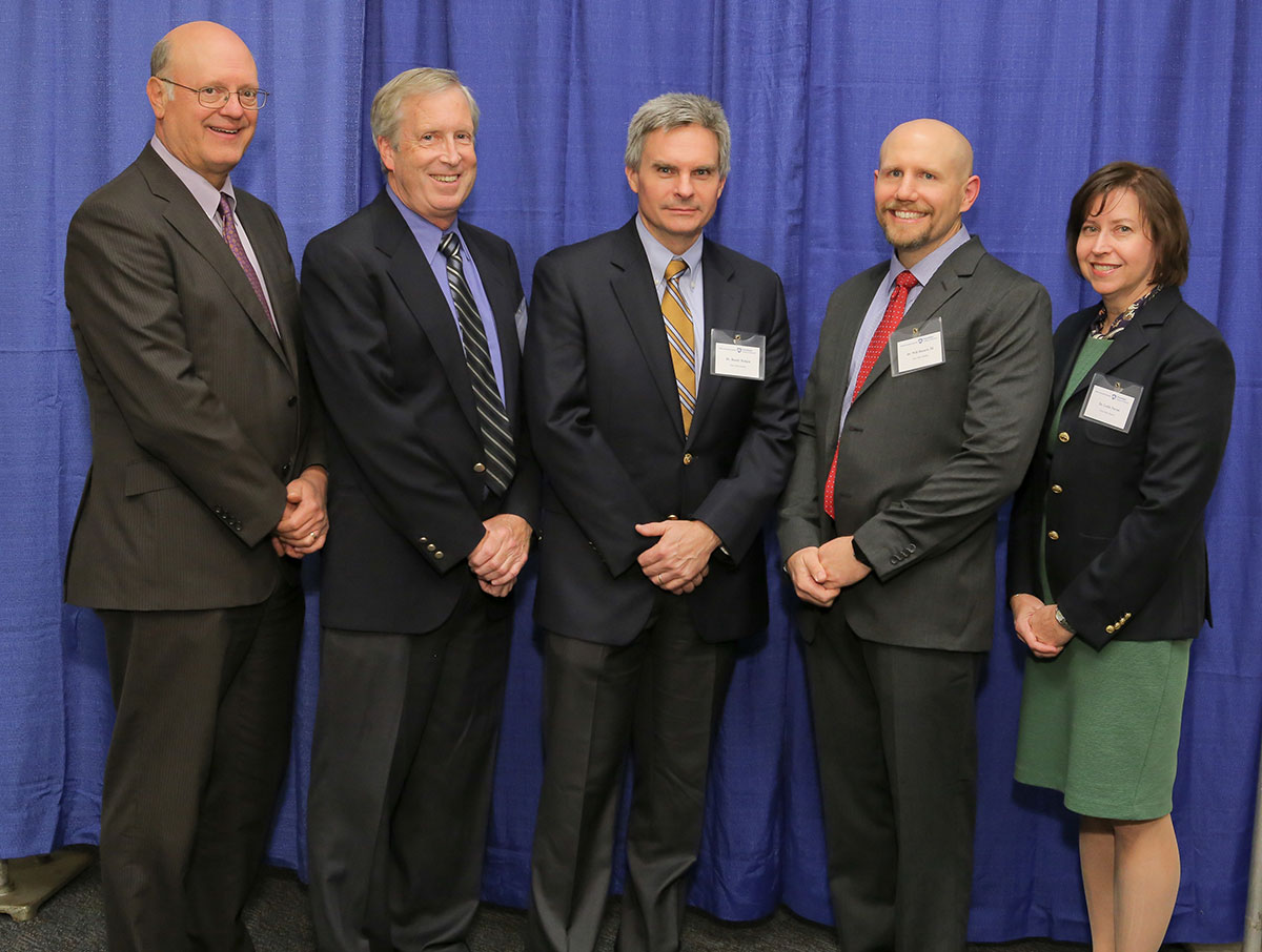 Penn State College of Medicine's 2016 Innovator of the Year award recipient is Will Hazard, MD, second from right. Hazard is pictured with, from left, A. Craig Hillemeier, MD, dean of the College and CEO of Penn State Health; Barry Fell, owner of TPC Design; Randy Haluck, MD, assistant professor of surgery at Penn State College of Medicine; and Leslie Parent, MD, vice dean for research and graduate studies for the College. The five are pictured standing in front of a blue photo backdrop.