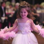Miracle Child Leah Myers smiles while wearing a dress and dancing.
