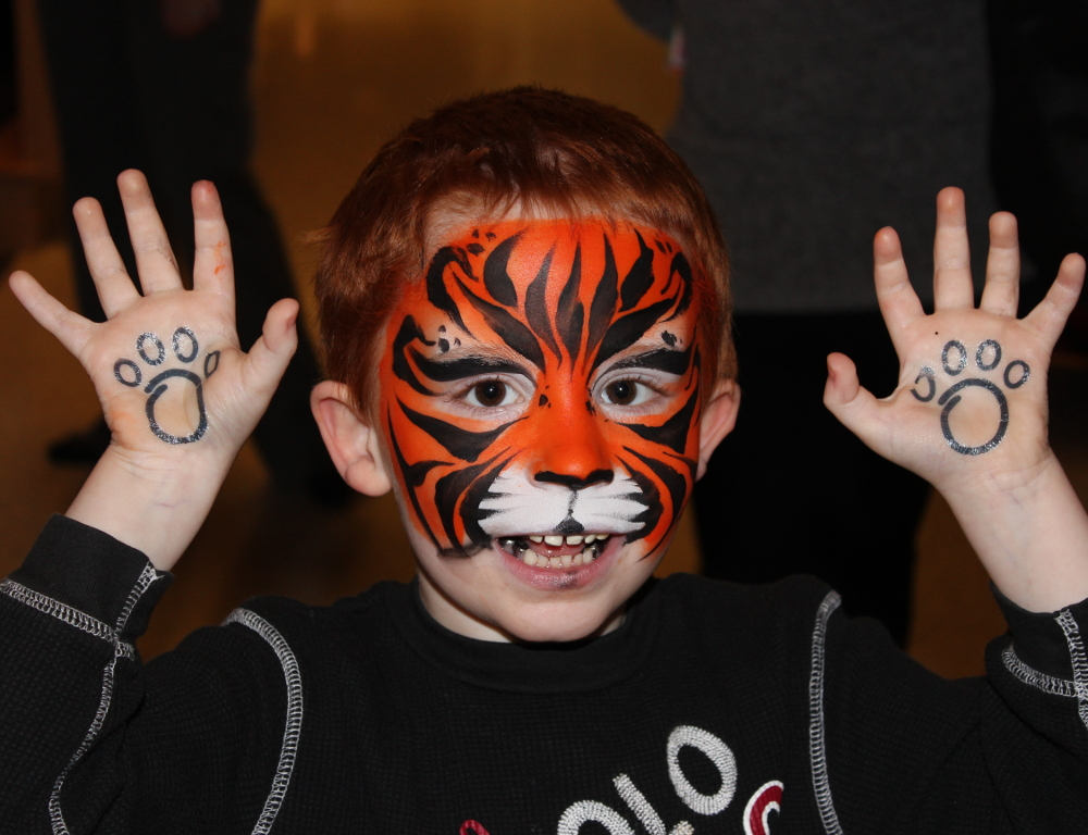 A child in tiger face paint holds his hands up, showing a paw print tattoo in each hand.