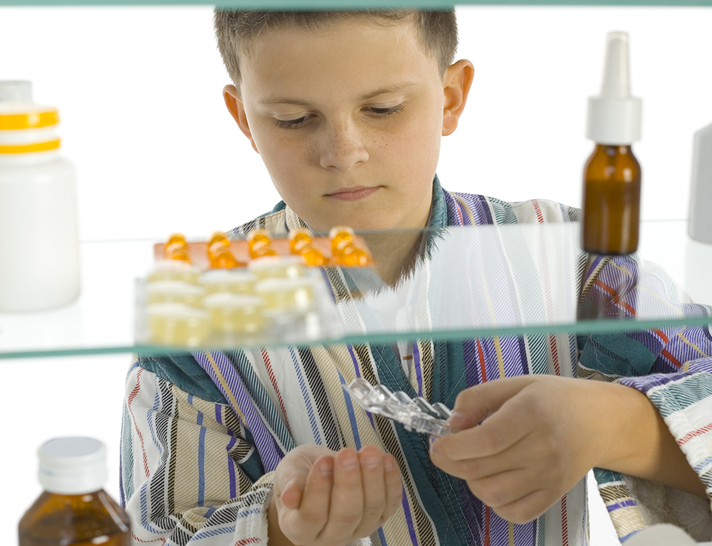 A child is seen through a medicine cabinet punching pills out into his hand. In the foreground, the cabinet contains several different medications.