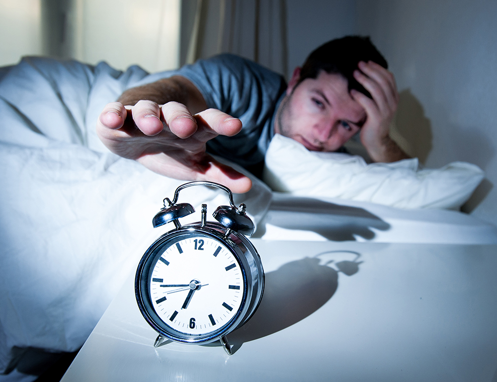 Man in bed reaches over to hit alarm clock.