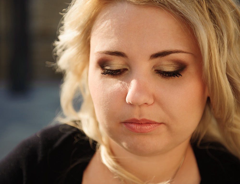 Blond woman with smoky eyes and make-up.