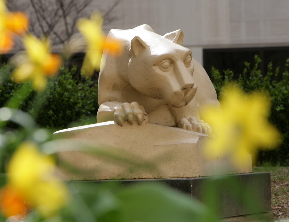 A close-up of a Nittany Lion statue on the Penn State College of Medicine campus. Yellow flowers are in the foreground, slightly out of focus.