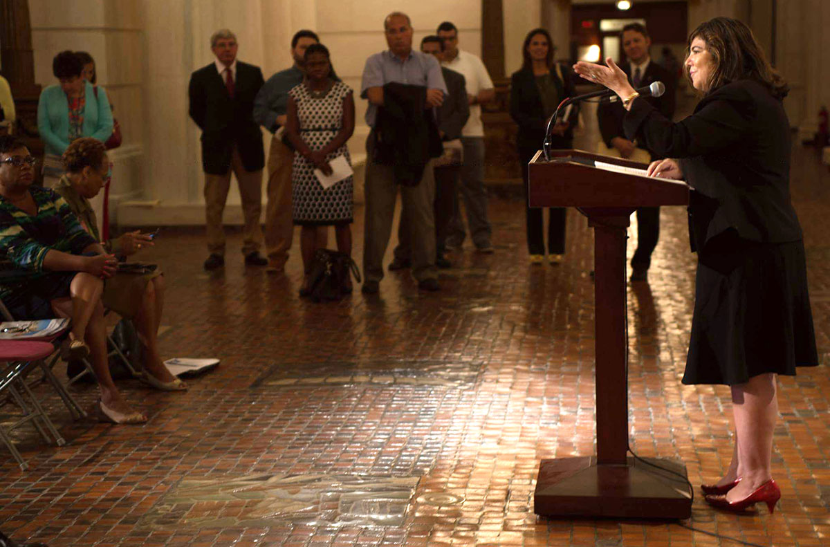 Dr. Oralia Garcia-Dominic discusses the first Pennsylvania Latino/Hispanic cancer burden report in September 2016 at the Pennsylvania State Capitol. Garcia-Dominic is pictured at right, standing at a podium and addressing a seated crowd seen at the left of the photo.