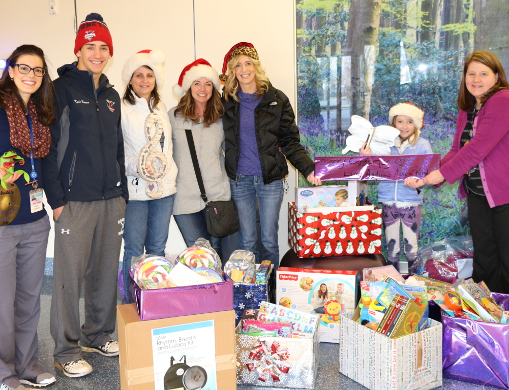 Seven people pose for a photo. In front of them are several boxes of gifts.