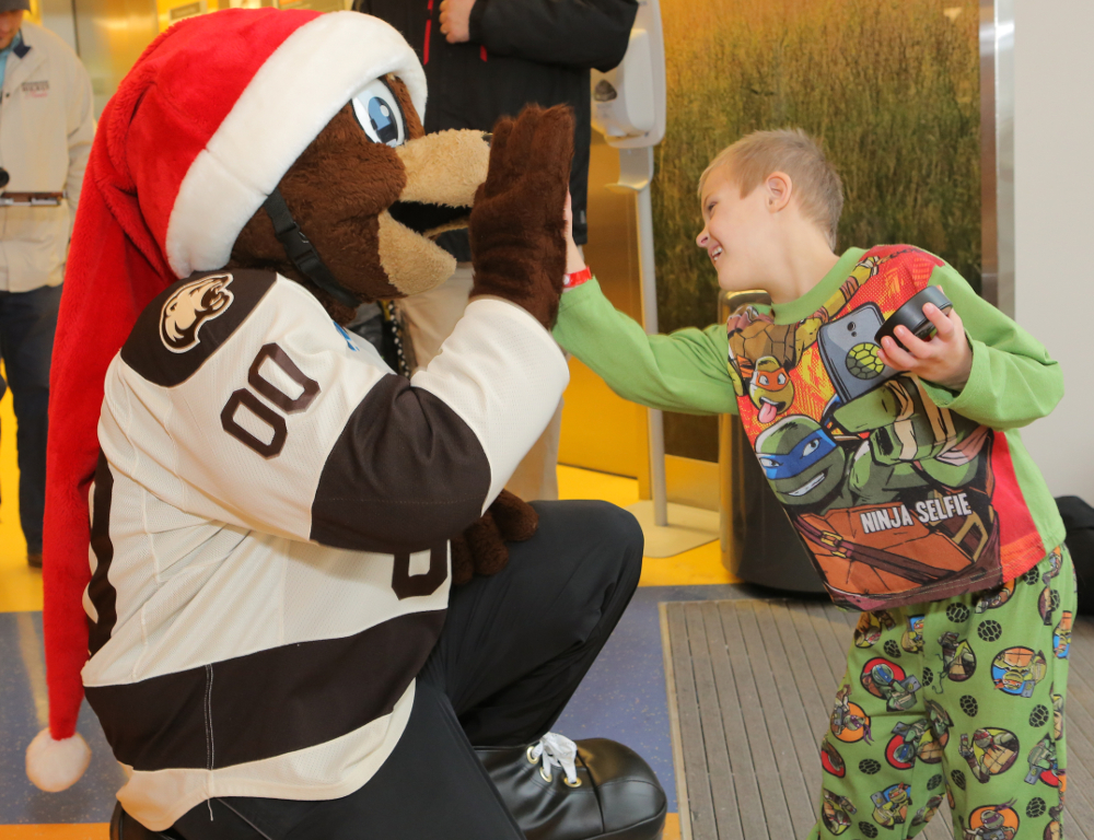 A young boy in Teenage Mutant Ninja Turtles pajamas smiles as he gives a high five to Coco, the Hershey Bears mascot.