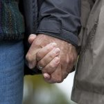 A close-up of two people holding hands