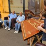 Two musicians, playing a hammer dulcimer and harp, perform as three people sitting nearby listen.