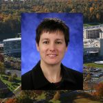 Sarah K. Bronson, PhD, was named Associate Dean for Interdisciplinary Research at Penn State College of Medicine in November 2016. She is pictured wearing a black dress shirt, in front of a dark blue photo background. Her picture is overlaid on an aerial view of Penn State College of Medicine's campus.