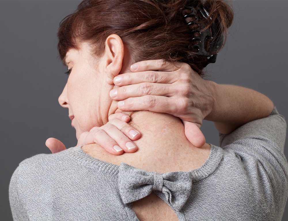 A woman places her right hand on the back of her neck. Her head is turned slightly to the left.