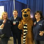 Three nurses and the Nittany Lion pose for a photo, in front of a blue pipe-and-drape background.