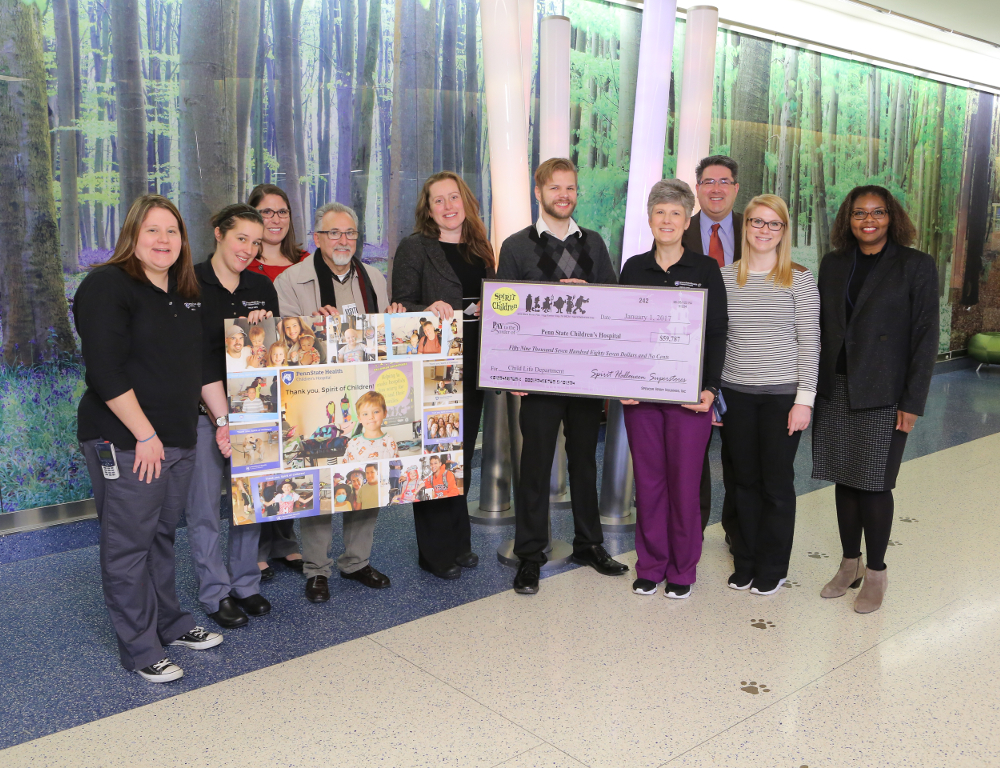Representatives of Penn State Children's Hospital and Spirit Halloween stores pose in the hospital lobby with an oversized check and a collage with photos of children.