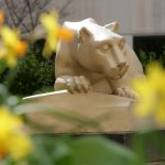 A statue of the Nittany Lion, with yellow flowers in the foreground, out of focus.
