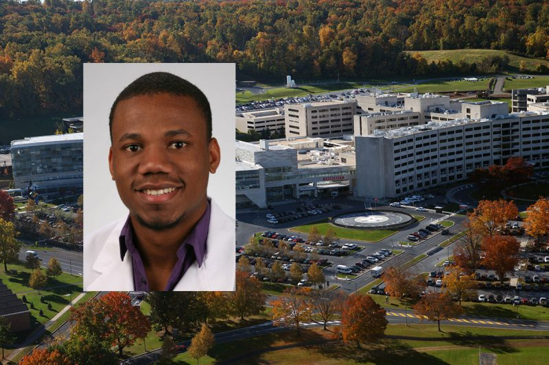 Penn State College of Medicine MD/PhD student Oliver Noel in his white coat is seen overlaid on an aerial photo of Penn State College of Medicine's campus in Hershey, PA.