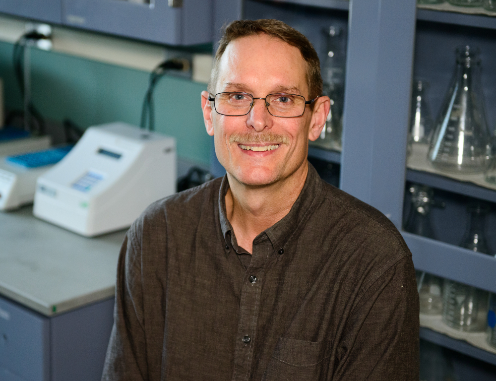 Jeffrey M. Peters poses for a photo, in a lab. He's wearing a brown shirt.