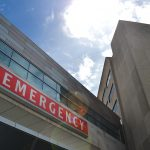 "A view of an ""Emergency"" sign -- white letters on red background -- looking up from the ground."
