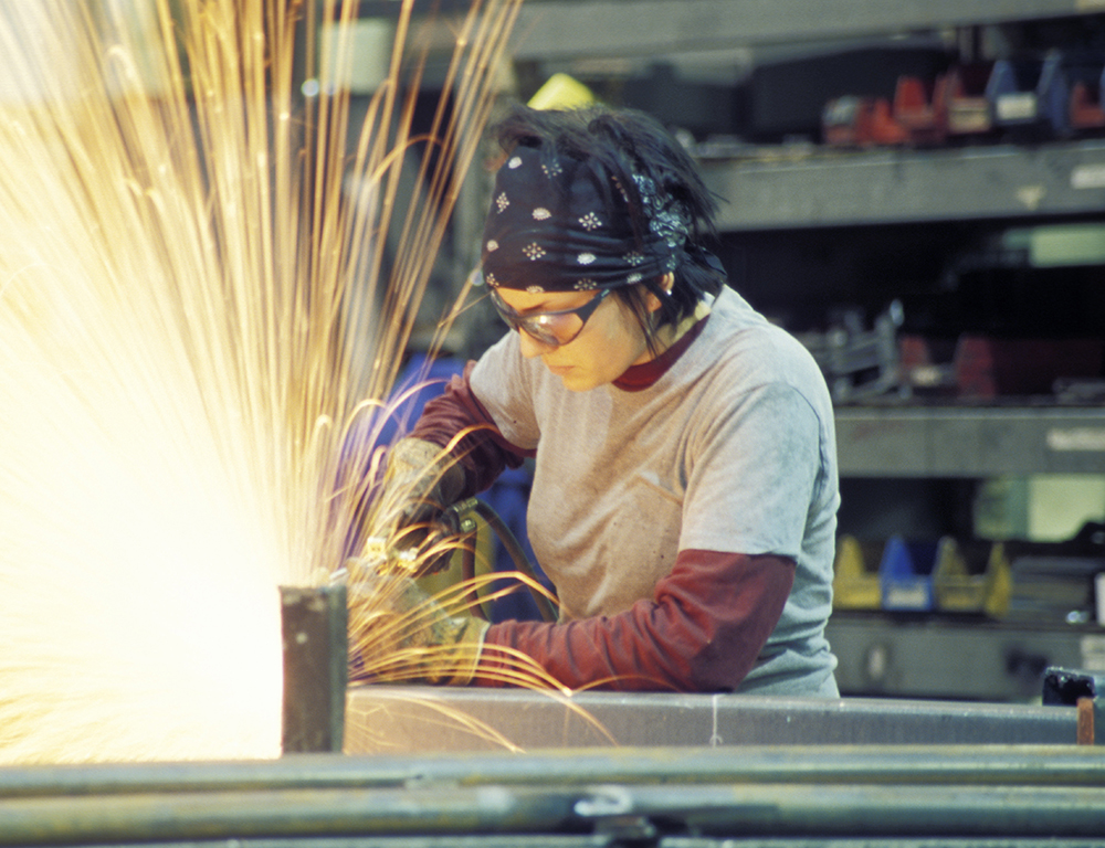 A woman wears goggles as she welds at a work table. Sparks fly up from the table into the air.