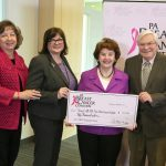 Four people pose with a check in the amount of $50,000. A backdrop with the PA Breast Cancer Coalition logo is behind them.