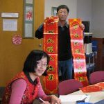 Members of Penn State College's Department of Cellular and Molecular Physiology held a celebration in honor of Chinese New Year. The holiday took place Jan. 28, 2017. Several members of the department are pictured in a conference room. One is holding a large banner with Chinese characters; others are looking at each other or the camera and smiling. Various food and other items are seen on the table in front of the group.