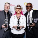 Nipsey, Jen Shade and Earl David Reed pose for a photo while holding small trophies, standing in front of a backdrop that has several CMN Hospitals logos.