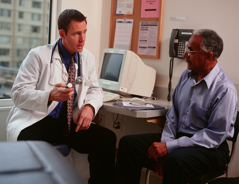 A physician sits at his desk talking with a patient. The physician is wearing a white coat and a stethoscope; the patient is wearing a blue shirt and dark pants.