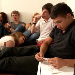 Six teenagers sit around a room. The teen closest to the camera is rolling a joint, another is smoking a cigarette, and two others are holding beer bottles.