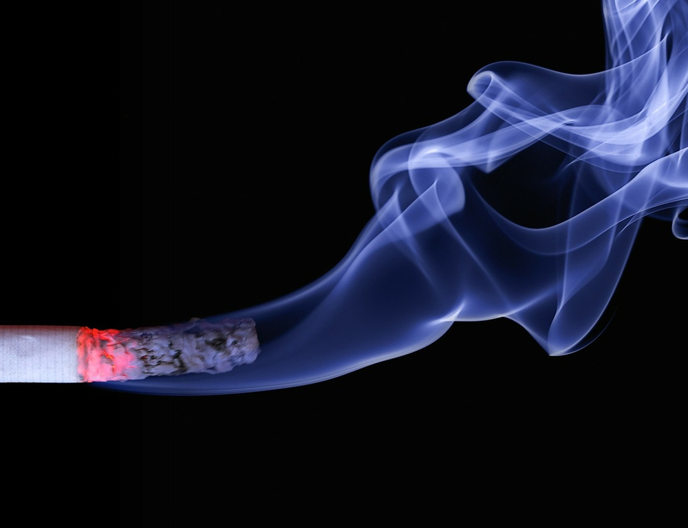 Close-up of a lit cigarette with a red tip and some residual ash on the end, with white smoke wafting upward, all against a black background.