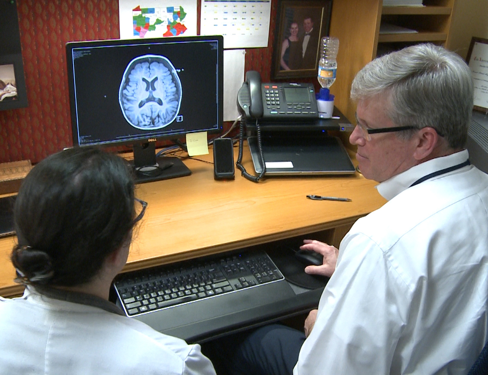 A man and a woman look at a computer screen on which a brain scan is depicted.