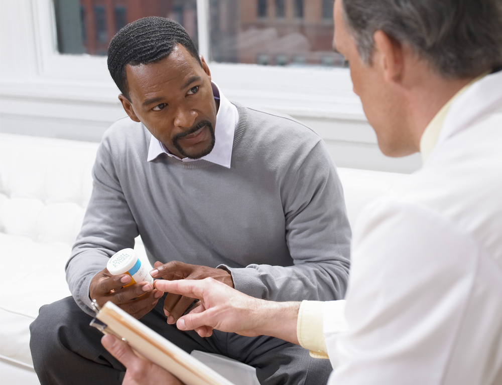 A male physician talks with a male patient. Both are seated. The physician holds a pad of paper; the patient holds a pill bottle and looks at the physician.