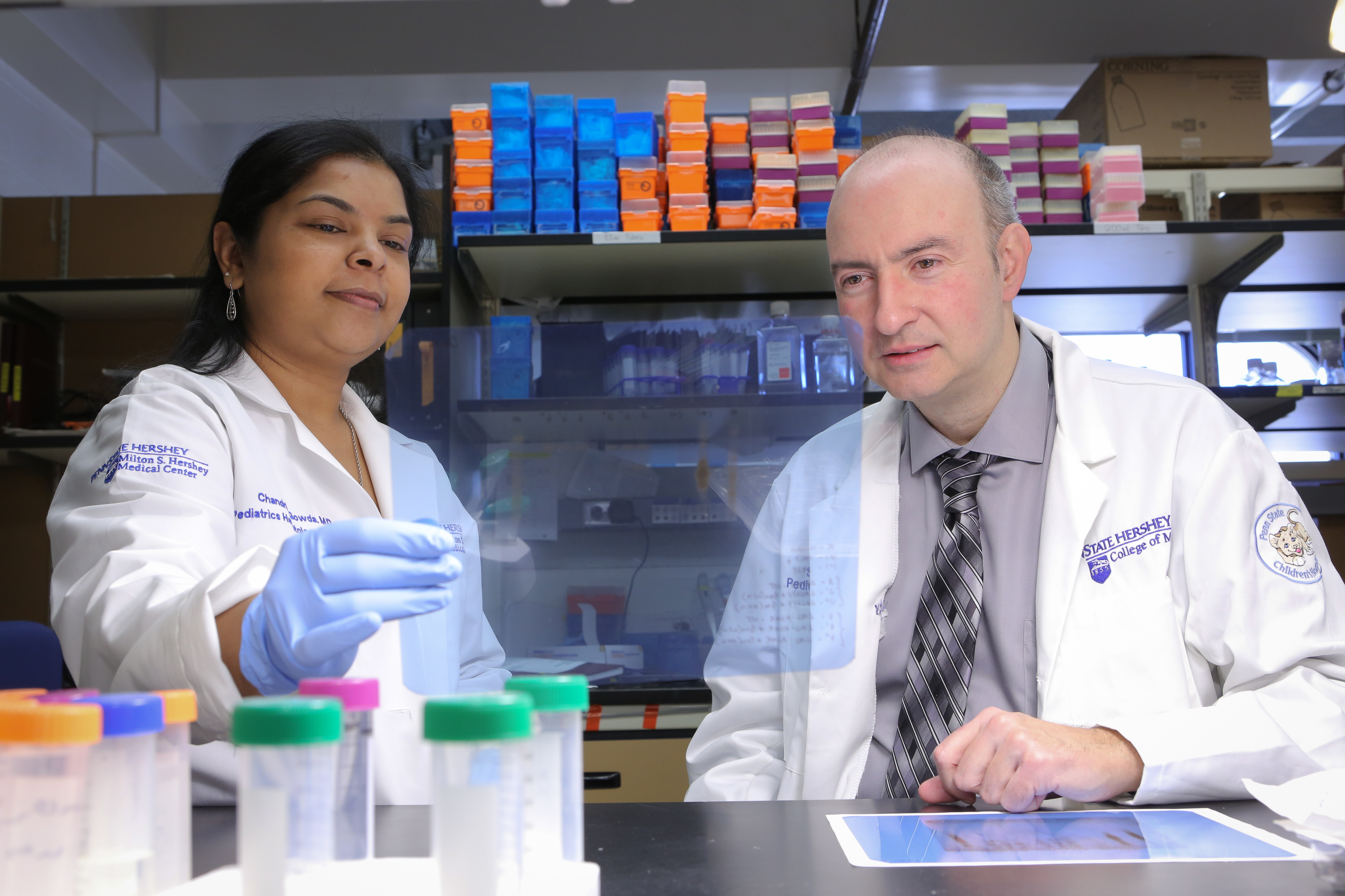 Dr. Chandrika Gowda is seen with her mentor, Dr. Sinisa Dovat. Gowda recently received a 2017 Young Investigator Award for her work in pediatric hematology/oncology. The two investigators are picture in a lab, with sample vials on the table in front of them and laboratory equipment visible in the background.