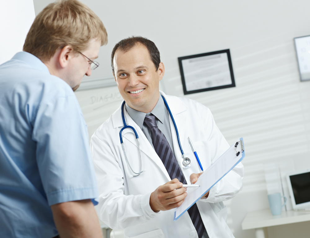 A male physician wearing a white coat and a stethoscope around his neck holds a clipboard with his left hand, using a pen in his right hand to point to the clipboard as a male patient looks down at it.