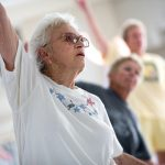 An older woman in the foreground is exercising by raising her right arm in the air. Two other people in the background are slightly out of focus.