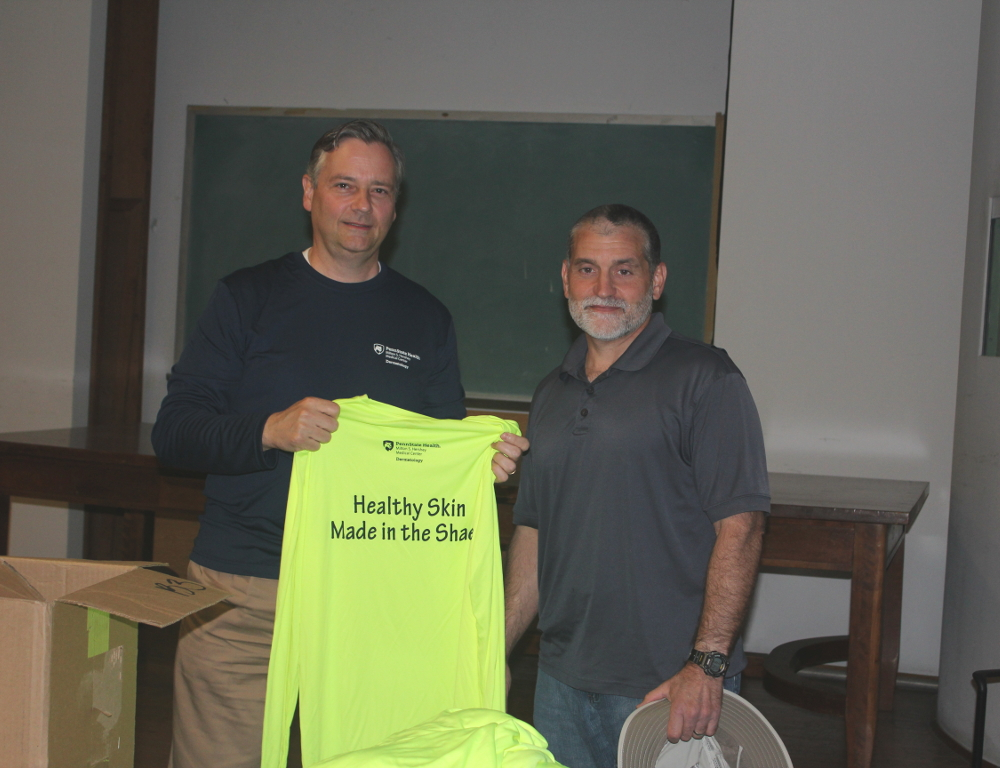 Two men pose for a photo. The man on the left holds a neon yellow shirt with the words Health Skin Made in the Shade printed on it. A table and chalkboard are in the background.