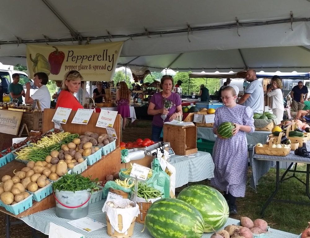 The inside of a tent at the Farmers Market in Hershey, with a table full of produce in the foreground and marketgoers browsing through produce and other goods at tables in the background.