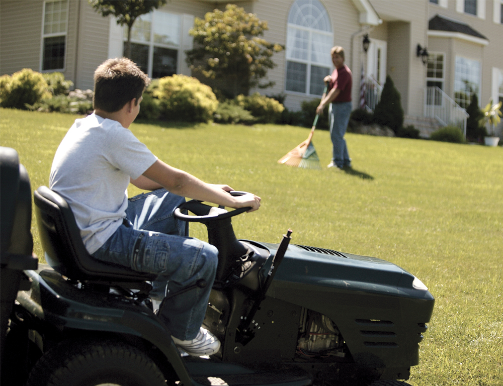 A teen sits on a riding mower in the front yard of a home. He looks uphill toward the house and a man raking grass.