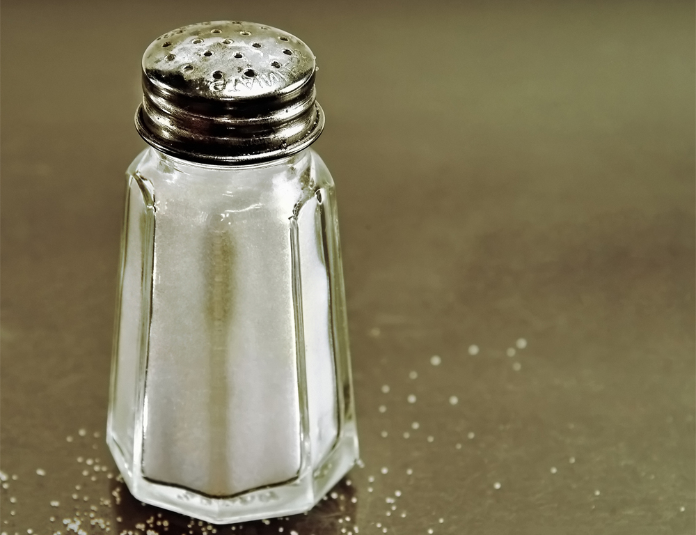 : A close-up of a full salt shaker sitting on a counter. A few grains of salt are sprinkled around it.